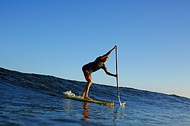 Paddle boarder riding ocean wave