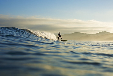 Silhouette paddle boarder riding ocean wave, Sayulita, Nayarit, Mexico