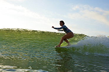 Female surfer riding ocean wave