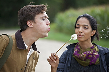 Couple blowing dandelion and making wish