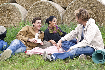 Men and woman resting in field and having drink