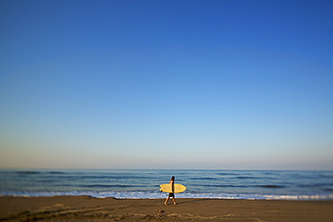 Male surfer carrying surfboard on sunny, tranquil beach, Platinitos, Nayarit, Mexico