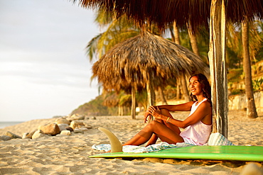 Female surfer with surfboard relaxing on sunny beach, Sayulita, Nayarit, Mexico