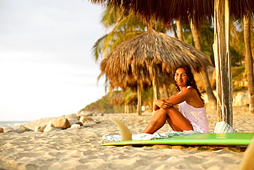 Portrait confident female surfer with surfboard relaxing on sunny beach, Sayulita, Nayarit, Mexico