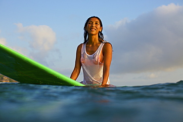 Smiling, confident female surfer waiting on surfboard in ocean
