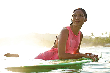 Confident female surfer leaning on surfboard in sunny ocean