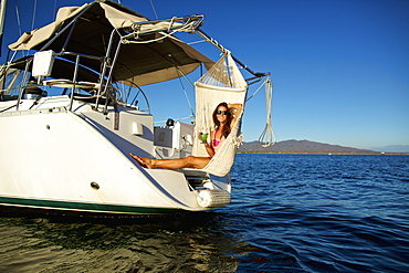Portrait carefree woman relaxing with cocktail in hammock on yacht over sunny ocean