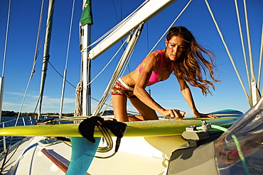 Female surfer waxing surfboard on sunny sailboat