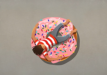 Girl relaxing on large donut with sprinkles