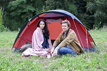 Young couple sitting near dome tent, portrait