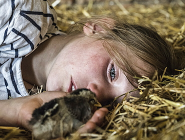 Close up girl holding baby chick in straw