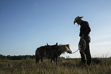 Cowboy with saddled pony in sunny rural field