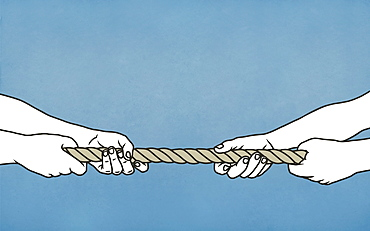 Couple playing tug-of-war with rope