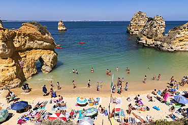 Tourists sunbathing and swimming on sunny, summer beach, Lagos, Algarve, Portugal