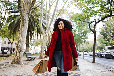 Portrait carefree young woman with shopping bags on urban sidewalk