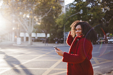Portrait confident, smiling young woman with smart phone on sunny city street