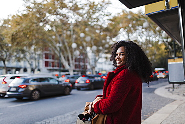 Smiling young woman on urban sidewalk