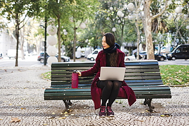 Woman with water bottle working at laptop in autumn city park
