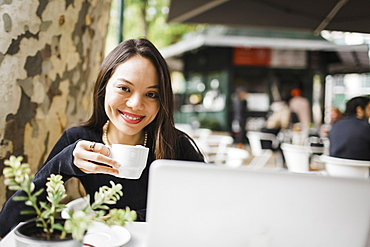 Portrait confident woman drinking coffee at laptop on sidewalk cafe