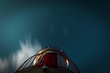 View from below lighthouse under starry night sky