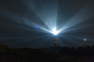 Light beacons illuminating from lighthouse under starry night sky, Wittduen, Germany