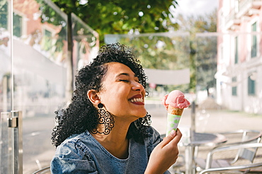 Carefree, excited young woman enjoying pink ice cream cone on sunny cafe patio