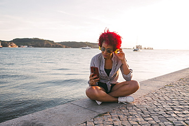 Woman with red hair listening to music with headphones and smart phone at waterfront, Portugal