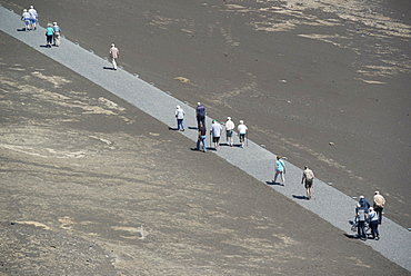 Tourists walking along volcano path, Faial Island, Azores, Portugal