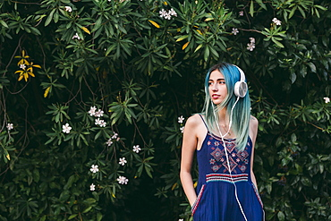 Young woman with blue hair listening to music with headphones in front of flowering tree