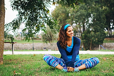 Smiling, fit female trainer exercising, stretching in park