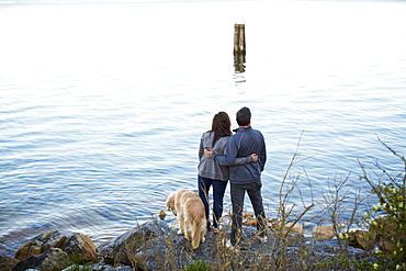 Affectionate couple with dog hugging, enjoying lake view