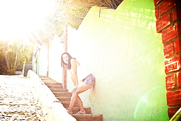 Woman on stairs leaning against sunny, vibrant wall