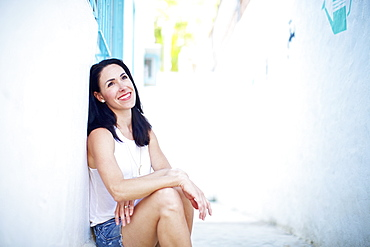 Portrait smiling, confident woman relaxing in summer alley