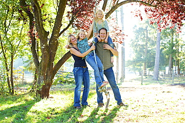 Portrait happy family on rope swing in sunny autumn park