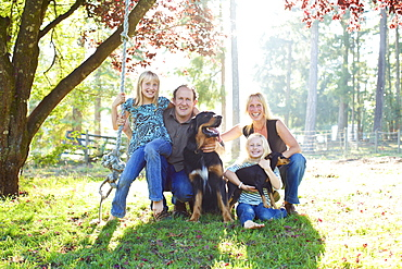 Portrait happy family with dogs in sunny autumn park