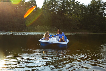 Mother and daughter paddleboating on sunny pond