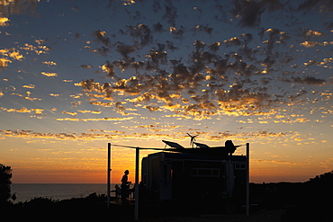 Clouds in dramatic sunset sky over silhouetted beach shack, Adelaide, Australia