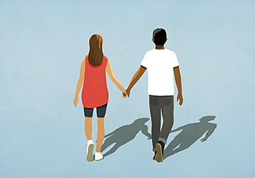 Multiethnic couple holding hands and walking