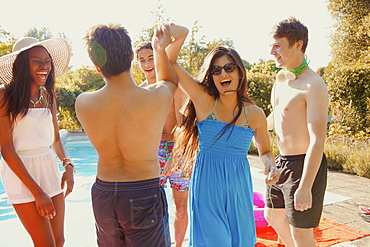 Carefree teenage friends dancing at sunny summer swimming pool