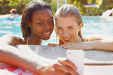 Teenage girl friends taking selfie with smart phone in summer swimming pool