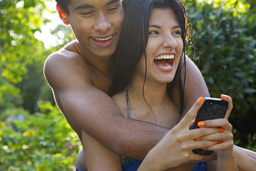 Happy, affectionate young couple using smart phone on summer patio