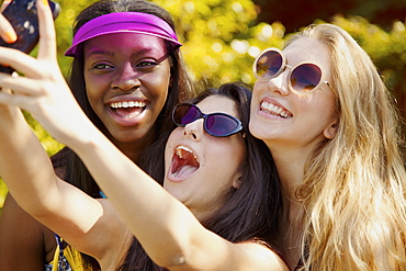 Happy teenage girl friends with sunglasses taking selfie