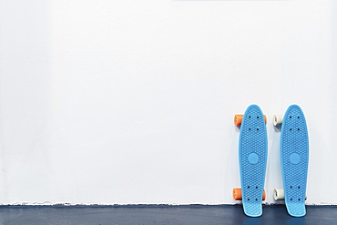 Blue skateboards leaning against white wall