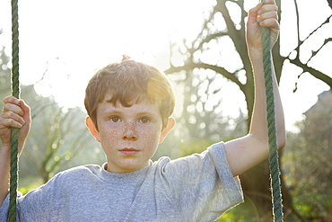 Portrait boy with freckles on rope swing in sunny garden