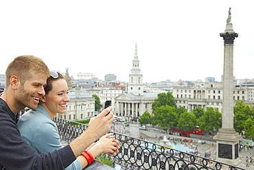 Happy couple using camera phone above Trafalgar Square, London, UK