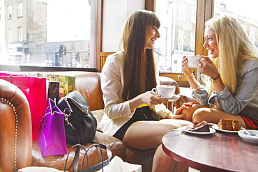 Young women friends with shopping bags enjoying coffee and dessert in cafe - 1177-3523