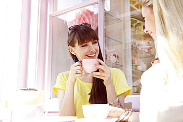 Happy young women friends drinking coffee in sunny cafe