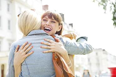 Happy young women friends hugging on sunny urban sidewalk