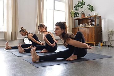 Flexible young women practicing yoga in yoga class