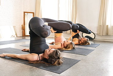 Young women practicing yoga in yoga studio